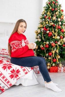 Een zwangere vrouw met een mok thee in een rode trui onder de kerstboom thuis streelt haar dikke buik en droomt van een baby en geniet van het nieuwe jaar en kerstmis