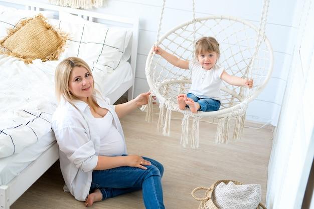 Een zwangere vrouw met haar dochtertje. baby die in een hangende stoel slingert, mamma die op de vloer zit.