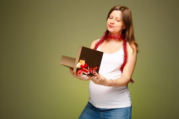 Een zwangere vrouw opent het cadeau met kerstmis met een ongelukkige gezichtsuitdrukking