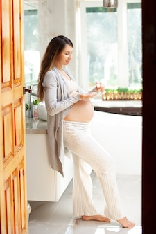 Een zwangere vrouw smeert haar buik in met crème van striae. huidsverzorging. badkamer, licht interieur. hoge kwaliteit foto. verticaal. binnen.