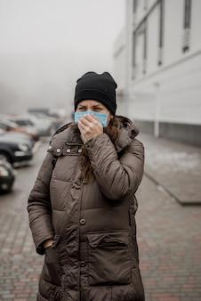 Een zwangere vrouw staat op straat in een europese stad tijdens een epidemie van coronavirus.