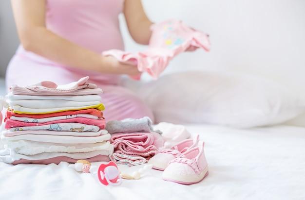 Een zwangere vrouw vouwt babydingen