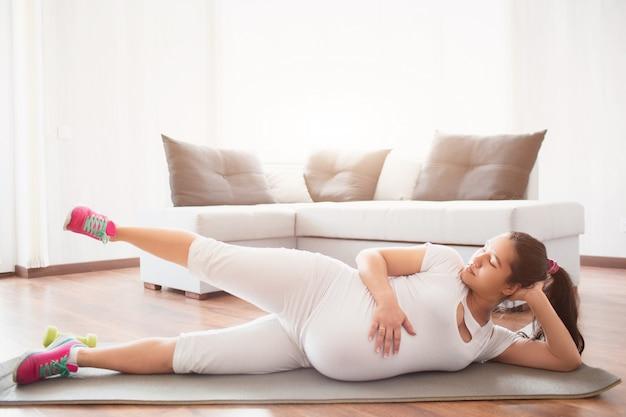 Een zwangere vrouw werkt thuis op een yogamat uit. zwangerschap en sport.