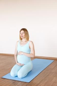 Een zwangere vrouw zit op een sportmat op een lichte achtergrond. yoga voor zwangere vrouwen. gezondheid van vrouwen. opladen voor zwangere vrouwen