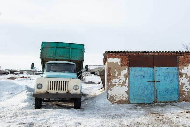 Een zware oude blauwe kiepwagen staat geparkeerd naast een gebouw te midden van witte sneeuw, wachtend op het begin van het laden. levering van goederen in de winter