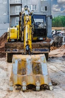 Een zware rupsgraafmachine met een grote bak maakt zich klaar voor het werk. zware bouwmachines voor grondwerken. steengroeve graafmachine. verbetering van het grondgebied.