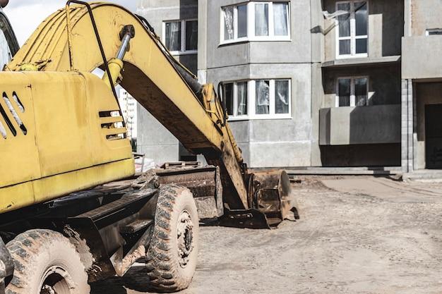 Een zware rupsgraafmachine met een grote emmer maakt zich klaar voor het werk voor een paneelhuis in aanbouw.. zware bouwmachines voor grondwerken. steengroeve graafmachine.