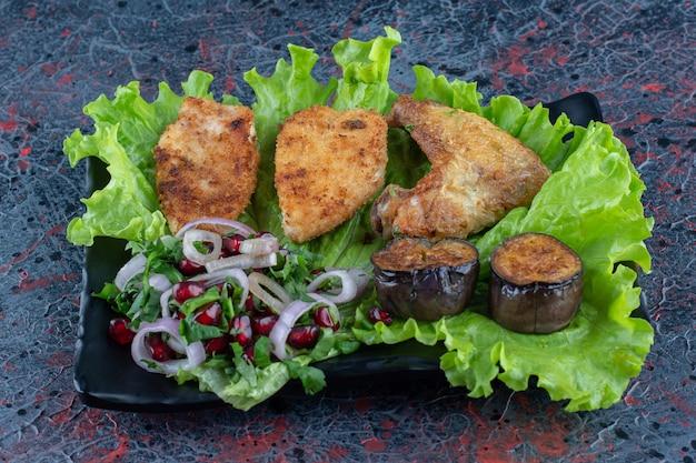 Een zwart bord kippenvlees met groenten