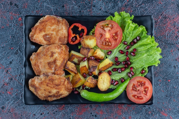 Een zwart bord met groenten en kipkoteletten
