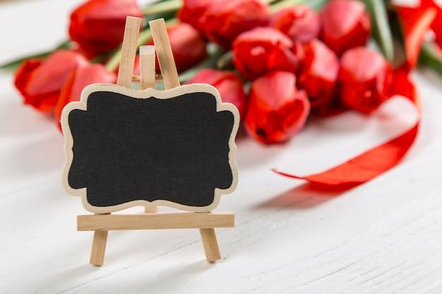 Een zwart bord tegen een van rode tulpen op witte tafel. het concept van moederdag. kopieer ruimte.