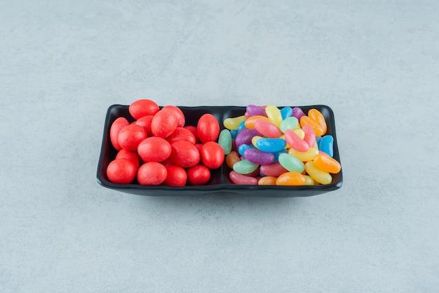 Een zwart bord vol kleurrijke bonensnoepjes op een wit oppervlak