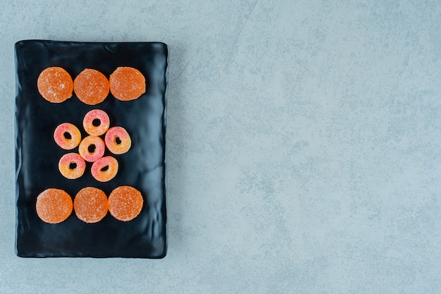 Een zwart bord vol ronde sinaasappelgeleisnoepjes in de vorm van ringen en oranje geleisuikergoed met suiker