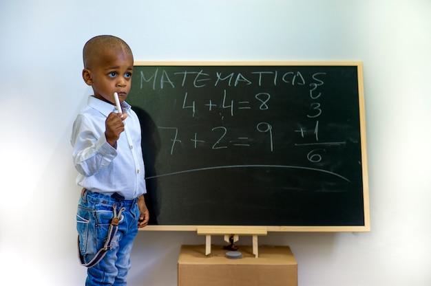 Een zwart kind dat op een schoolbord schrijft