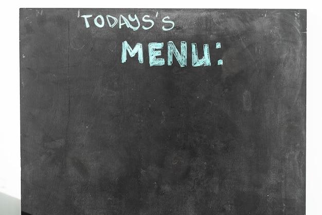Een zwart krijtbord met menutekst in het straatrestaurant