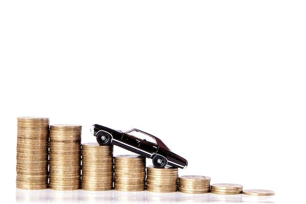 Een zwart model van een auto met munten in de vorm van een histogram op een witte achtergrond. concept van leningen, besparingen, verzekeringen.