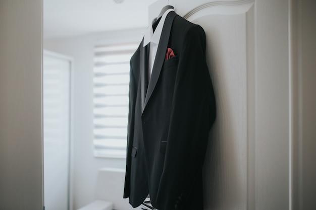 Een zwart pak en een wit overhemd hangen aan de hanger aan de deur