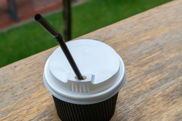Een zwart papieren koffiekopje met deksel buiten in de zomer bij zonnig weer op een houten tafel van een café, koffieshop of restaurant.