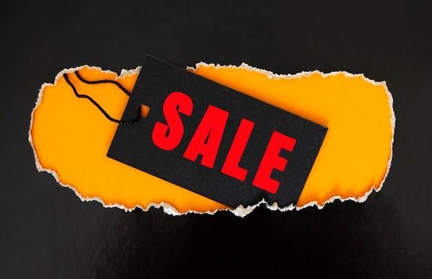 Een zwart rechthoekig kledinglabel rust op gescheurd zwart papier. gele achtergrond. verkoopconcept.
