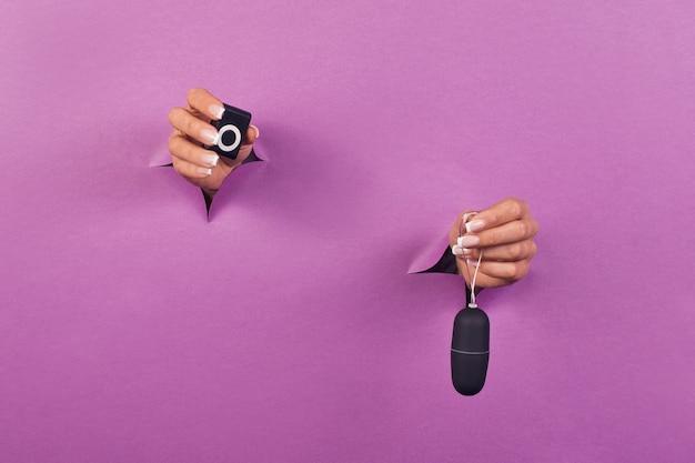 Een zwart siliconen seksspeeltje op roze achtergrond in vrouwelijke handen