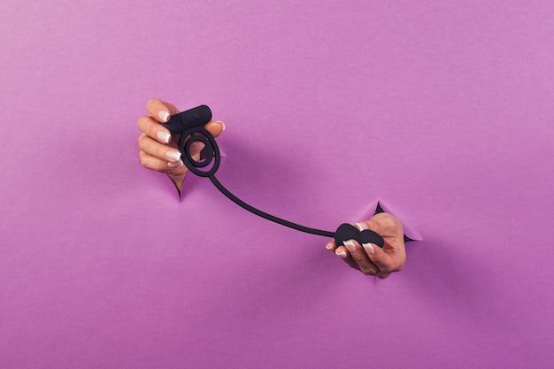 Een zwart siliconen seksspeeltje voor de clitoris op een roze achtergrond in de handen van een vrouw