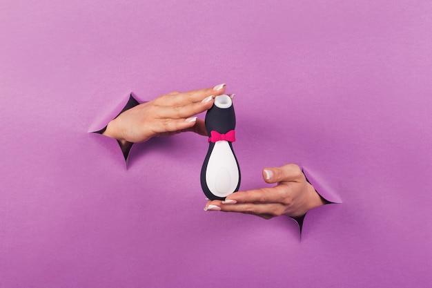 Een zwart-wit pinguïn siliconen seksspeeltje op roze achtergrond in vrouwelijke handen erotisch speeltje voor de lol
