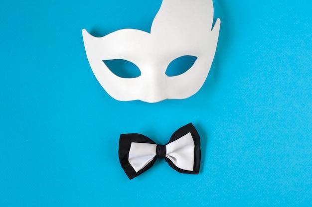 Een zwart-witte vlinderdas en een wit carnavalsmasker op een pastelblauwe achtergrond. ruimte kopiëren.