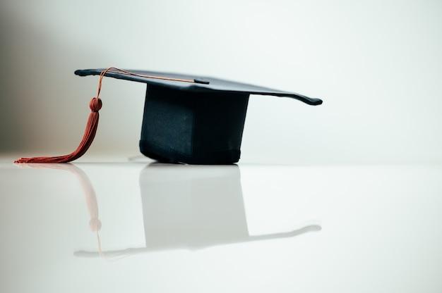Een zwarte afstudeerpet met een bruine kwast wordt op de glazen vloer geplaatst