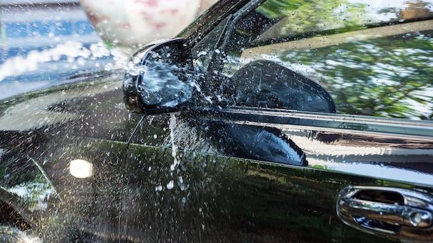 Een zwarte auto wassen met water onder hoge druk.