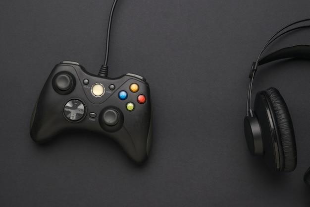 Een zwarte console voor computerspelletjes en zwarte koptelefoons op een zwarte achtergrond. een apparaat voor het spelen van computerspelletjes. plat leggen.