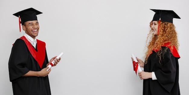 Een zwarte en roodharige studenten in afstudeerjurken en vierkante petten staan tegenover elkaar met hun gekoesterde diploma banner met kopieerruimte