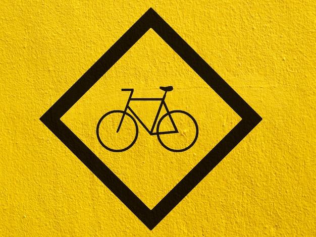 Een zwarte fietspunten die op een gestuukte muur buiten zijn geschilderd