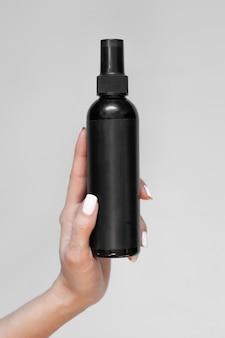 Een zwarte fles cosmetische spray met een leeg etiket in de hand van een vrouw op een lichte achtergrond