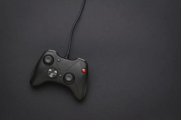 Een zwarte gameconsole met een draad op een zwarte achtergrond. een apparaat voor het spelen van computerspelletjes. plat leggen.