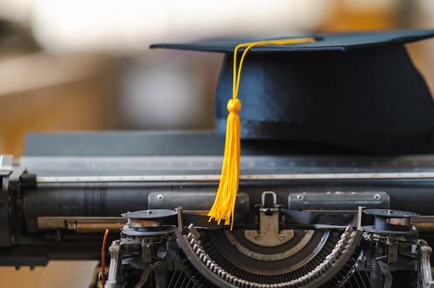Een zwarte hoed met een gele kwast van een afgestudeerde wordt op een typemachine geplaatst.