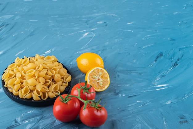 Een zwarte houten plaat van rauwe pasta met citroen en verse rode tomaten.
