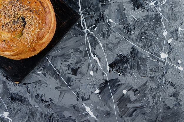 Een zwarte houten plank van azerbeidzjaanse gohal op een marmeren tafel.