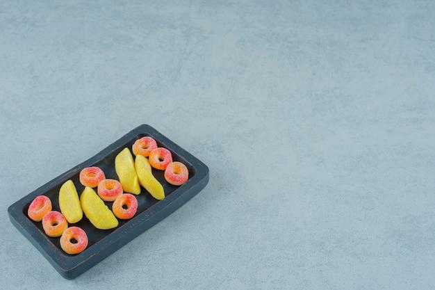 Een zwarte houten plank van banaanvormige kauwsnoepjes met ronde oranje gelei snoepjes in de vorm van ringen