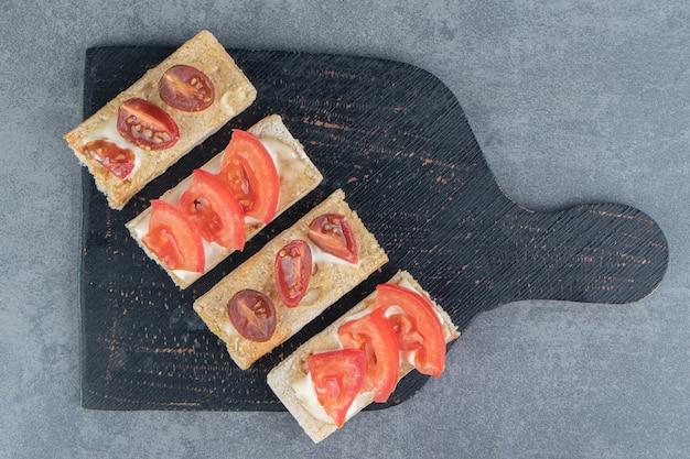 Een zwarte houten plank van krokante toast met tomaten.