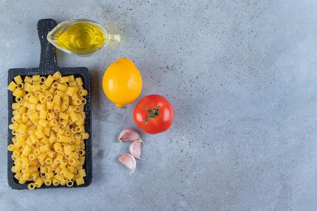 Een zwarte houten plank van rauwe droge ditali rigati pasta met verse rode tomaat en olie.