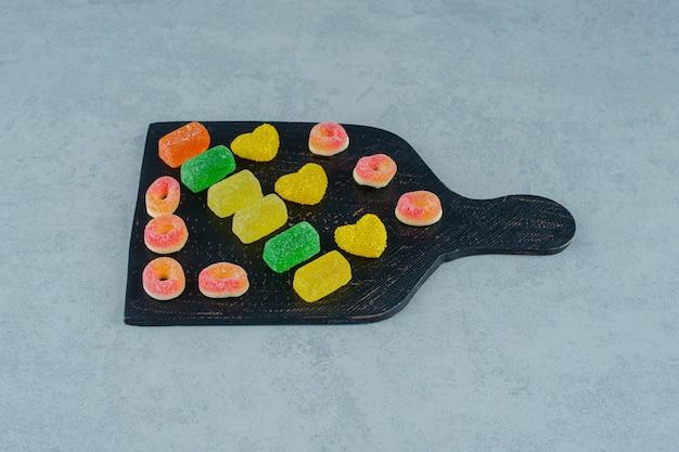 Een zwarte houten plank vol kleurrijke fruitsnoepjes op een witte ondergrond