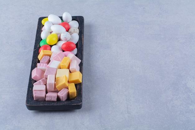 Een zwarte houten plank vol kleurrijke, suikerachtige fruitmarmelades