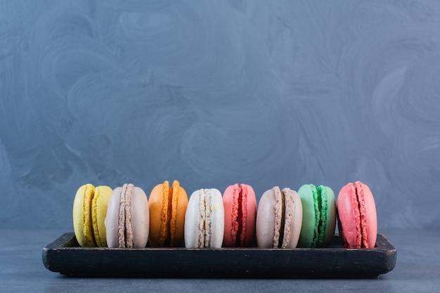 Een zwarte houten plank vol macaroni koekjes in verschillende kleuren