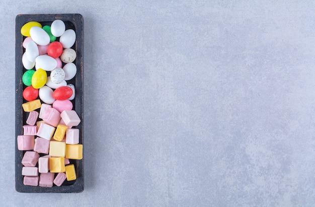 Een zwarte houten plank vol met zoete kleurrijke snoepjes. hoge kwaliteit foto