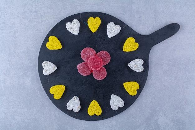 Een zwarte houten plank vol zoete gelei snoepjes.