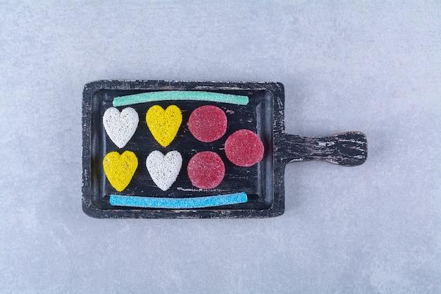 Een zwarte houten plank vol zoete, kleurrijke snoepjes