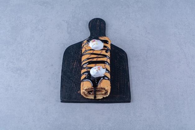 Een zwarte houten snijplank van zoet heerlijk broodje met chocoladesiroop en room.