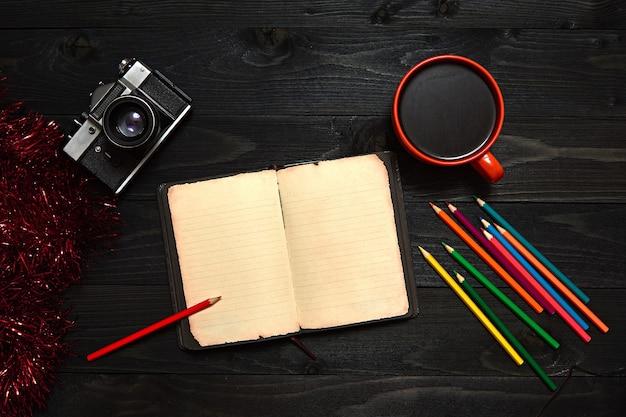 Een zwarte houten tafel met kleurpotloden, een notitieboekje, een camera en een oranje koffiemok