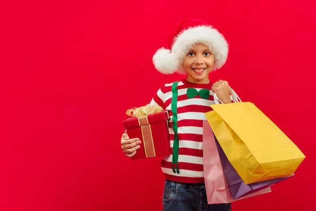 Een zwarte jongen met een kerstmuts houdt cadeaus en papieren zakken in zijn handen voor kerstinkopen van vrienden