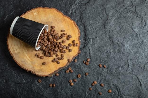 Een zwarte kop vol koffiebonen op een houten bord.