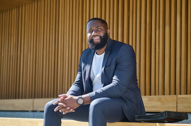Een zwarte man die op de bank zit te wachten op iemand
